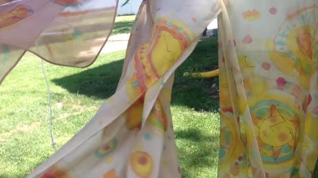 Silk scarves with sun motif blowing in breeze
