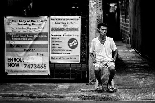 Old man, sitting intently by the street.